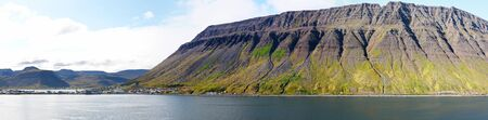 Isafjordur, Iceland. Panoramic view of Rugged Mountain coastline. Summer Cloudy blue sky. Mountain landscape seen from sea.