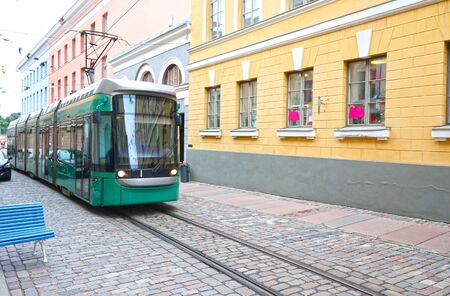 Green Tram on Narrow Street of City Center at Helsinki, Finland. HSL HRT Transit System  is One of the oldest electric tram networks in the world.