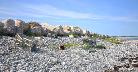 Old abandoned broken lobster traps Littering a gravel beach at Nova Scotia, East coast of Canada.