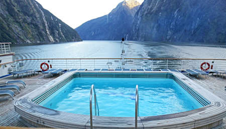 Stern View of Cruise Ship sailing pass Fiordland National Park, South Island, New Zealand. Misty Cloudy Morning