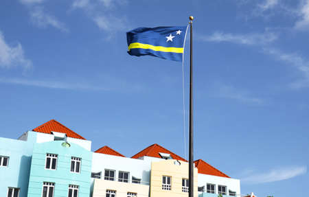 Willemstad, Curacao. Dutch Antilles.  National flag with Colourful Buildings attracting tourists from all over the world. Blue sky sunny day.