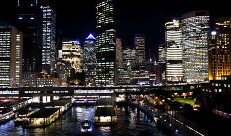 Night view of Downtown Sydney Skyline.  Illuminated Highrises and Office Towers. Sydney Ferry wharf area.