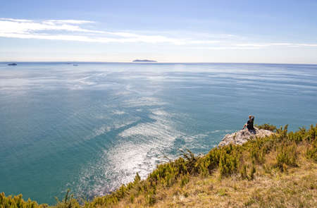 Tauranga, New Zealand. Hiker sitting resting enjoying Panoramic sea view from Mount Maunganui. Tauranga is a major cruise ship outdoor nature destination on northern island. Person materially altered