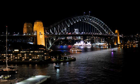 Night view of Sydney harbor bridge and North Sydney, boats sailing in the bay and Parramatta River. Focus on Bridge.
