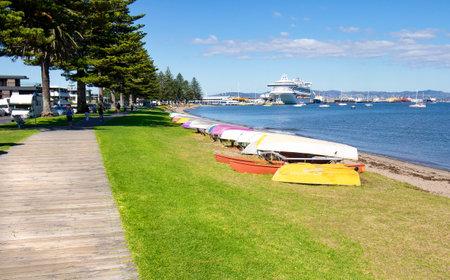 White sand beach walkway path. Tauranga is a major cruise ship destination on northern island of New Zealand.  Focus on boats on grass