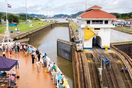 Panama Canal, Panama - Oct 13, 2018: Cruise ship Approaching  opened gates of Miraflores Lock. This is the narrower Original historic Panama Canal, Panama.  Cruise ship tourists on Bow of ship. Publikacyjne