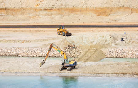 Suez Canal construction site. Backhoe and Frontend Loader working in the sandy bank. View from the water, Suez Canal, Egypt Zdjęcie Seryjne