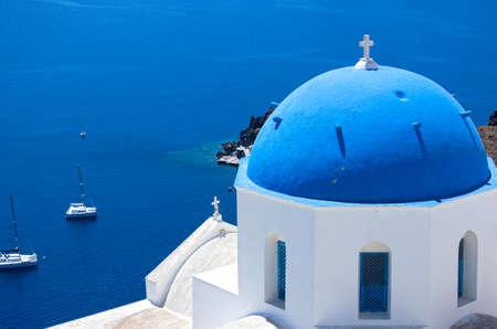 Oia town in Santorini, Greece.  Blue domed churches Agios Spyridonas and Anastaseos.