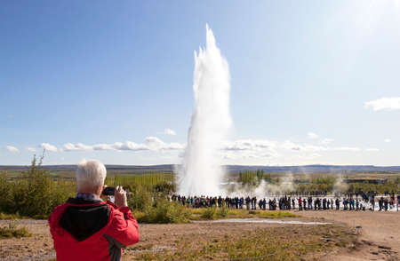 Iceland Geyser Strokkur Eruption on a beautiful sunny summer day, with unrecognizable faces tourists Zdjęcie Seryjne