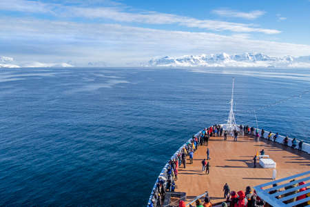 Tourists on Cruise Ship's Bow Deck.  Heading to Antarctic Peninsula, Ice covered Land in the Distance
