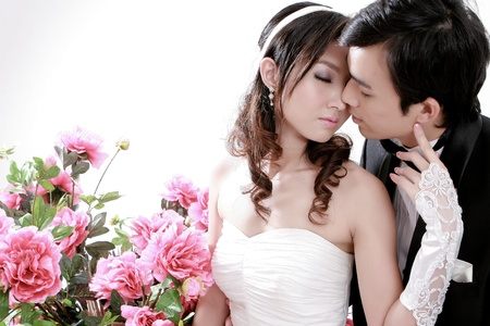 Portrait of young bride and groom kissing each other with sweet floral backgroung