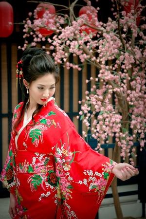 Portrait of young beautiful girl in red kimino dress touching sakura flower