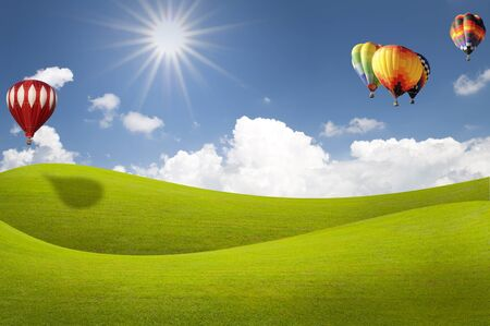 Grass field with sunlight and balloon over blue sky photo