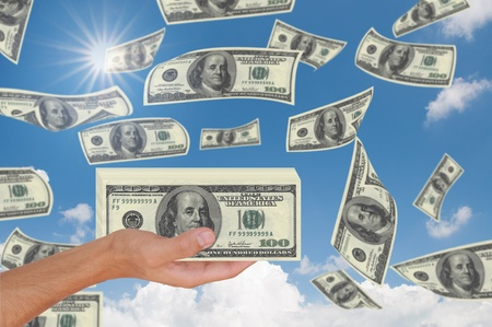 Male Hand Holding Stack of Cash Over beautiful sky photo