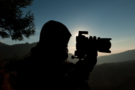 film shooting: Silhouette of a cameraman against a sunrise