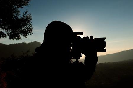 movie camera: Silhouette of a cameraman against a sunrise