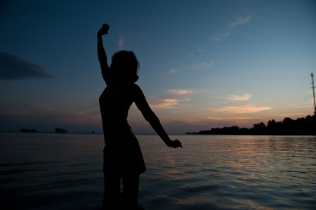 Silhouette of happy woman at the sea photo