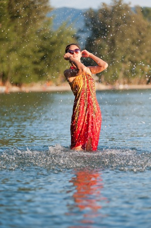 Cute asian girl splashing out of the water photo