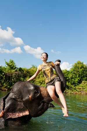 Cute asian girl sitting on Proboscis of elephant while bathing in a pond Stock Photo
