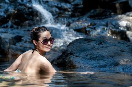 Sexy asian girl looking back  when she bathing in the waterfall photo