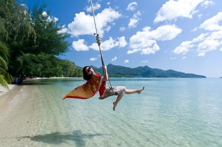 girl on swing: Beautiful asian girl play swing at the sea