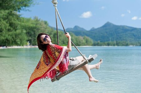 Beautiful asian girl play swing at the sea photo