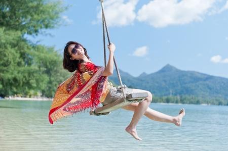 Beautiful asian girl play swing at the sea