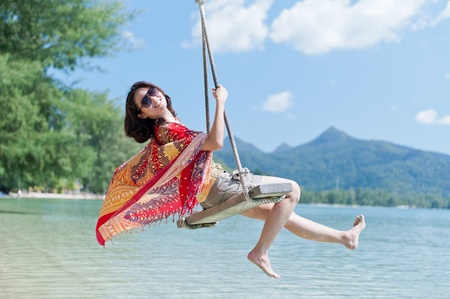 columpio: Hermosa muchacha asi�tica columpio jugar en el mar Foto de archivo