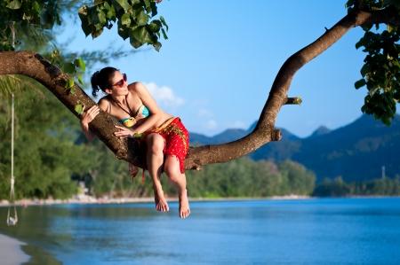 piedi nudi di bambine: Sexy ragazza asiatica sedersi sul tronco dell'albero a Koh Chang spiaggia, Thailandia