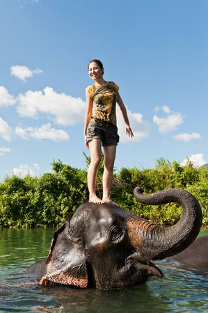 Cute asian girl standing on the head of elephant while bathing in the pond photo