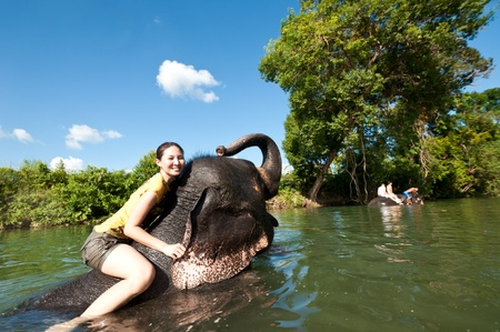 Cute asian girl standing on the head of elephant while bathing in the pond