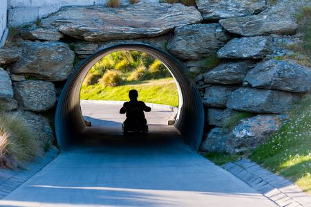 Silhouetted view of man play luge pass tunnel photo
