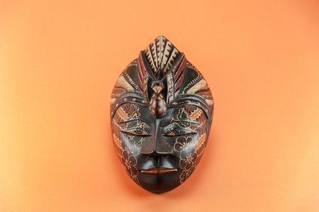 Batik wooden indonesian mask isolated on orange background Stock Photo