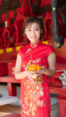 Asian girl in red dress. Chinese New Year.Cheongsam dress Stock Photo