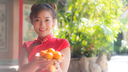 Asian girl in red dress holding orange Chinese New Year