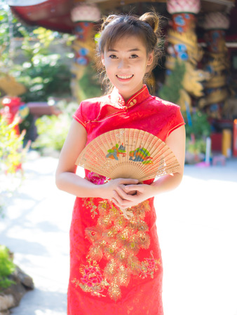 Asian girl in red chinese costume blowsChinese New Year