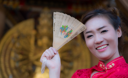 Standing fan holds a souvenir from China. Asian girl dress up Chinese New Year