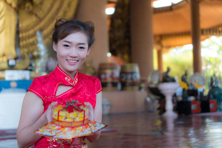 Asian girl wearing a Chinese New Year dress Lovely smile Send the red envelope in Chinese New Year and would like to give a spring roll as a gift in Chinese New Year. Stock Photo