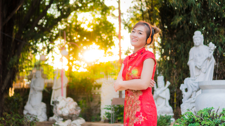 Beautiful Asian girl wearing Cheongsam red dress listening to music be happy. the celebration of something in a joyful and exuberant way. select focus