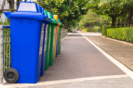 Row of Wheelie Bins. Many trash carts set in the park. There are blue, green and yellow tanks. Copy space. Foto de archivo - 100961960
