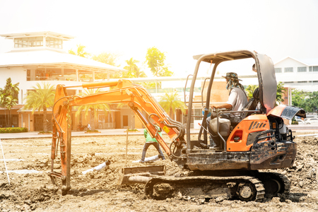 Heavy orange machine crawler loader or loader excavator, removing soil from ground for laying pipes And site preparation at a civil construction site.