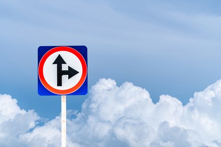 Traffic signs say it is a junction. Can be straight and turn right. Sky background. Copy space.