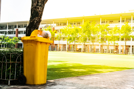 Recycle bin : Yellow bins are located on the sidewalk beside the lawn. concept of environmental protection.