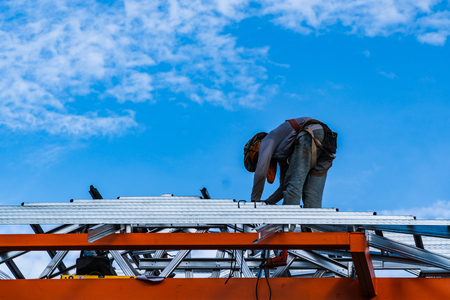 Construction worker is working By installing the roof of the house. The background is sky and clouds. Standard-Bild