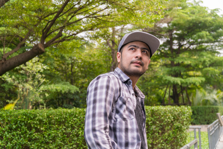 Portrait Handsome man : Good looking young man. He has a beard and wears a hat. He has an interesting smile. Looking for someone. Behind him, full of green trees. Copy space. 写真素材