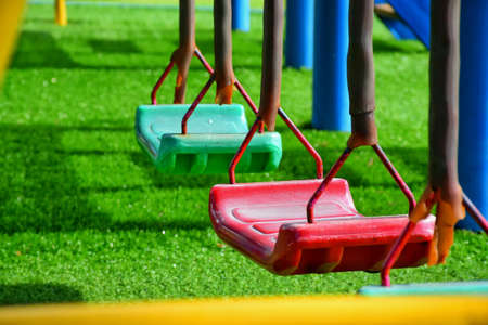 Swing kids in playground Stock Photo