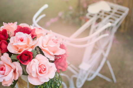 The roses in basket on white bicycle with blurred background. Valentine day concept. Wedding concept.