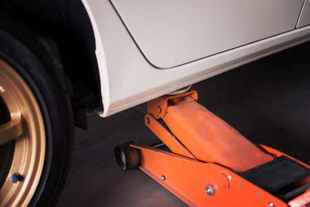 winter tires: Car Lifted with blue hydraulic floor jack for repairing.
