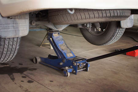 Car Lifted with blue hydraulic floor jack for repairing.