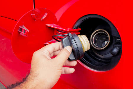 automobile door: Close up shot of a cars. Open fuel tank lid in red car. Refueling a car at a fuel station.